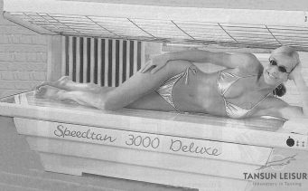 Woman Tanning in Tansun's First Commercial Lay Down Sunbed, the Speedtan 3000 Deluxe, Launched in 1990